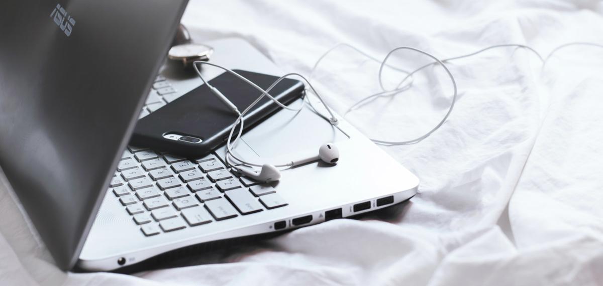 Tietokone, matkapuhelin ja kuulokkeet.